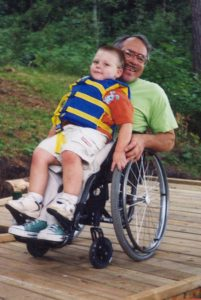 Older man in a wheelchair on a dock. He holds a young boy on his lap.