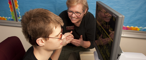Teacher assisting student with screen magnifier