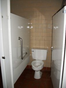 Undersized restroom stall with inswing door and no rear grab bar