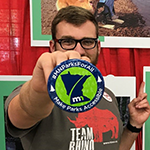 "Man holding a button that reads: ""MN Parks For All, Make Parks Accessible."" In the background are photos of people with disabilities enjoying state parks."