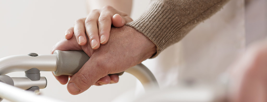 Close up of a man's hand holding on to a walker. A woman's hand rests on top of his.