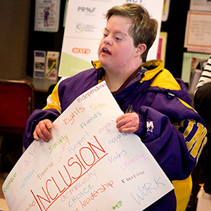 Disability advocate holding a poster. The most prominent word, among a group of such, is Inclusion.
