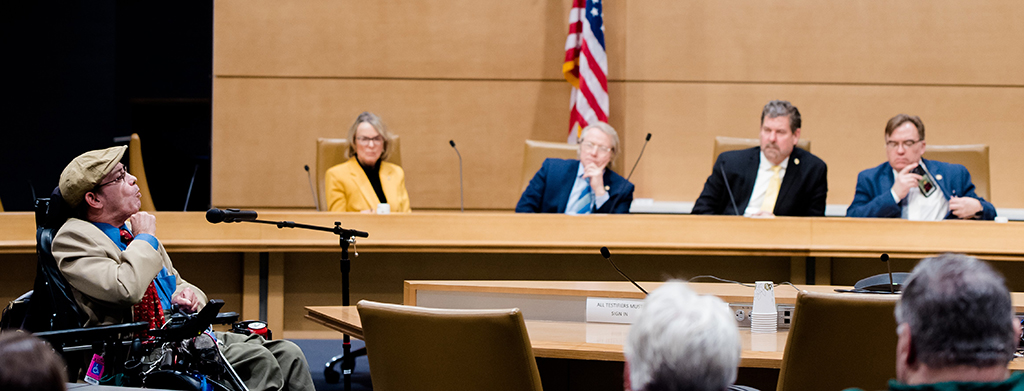 Man who uses a wheelchair speaking to four legislators, American flag in background