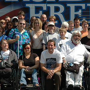 "Rick Cardenas in a group photo with the disability community, in front of the ""Road To Freedom"" bus."
