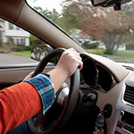 A woman holds the steering wheel of a car while driving down the road.